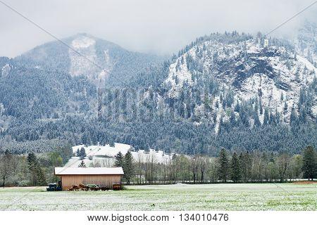 Barn Of Farmhouse. Spring Snow In Meadows Bellow Mountains.