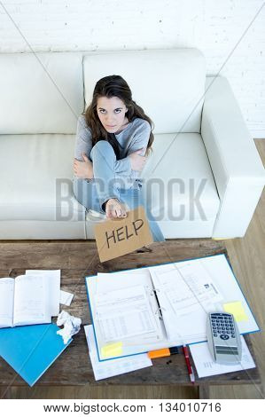 young woman asking for help suffering stress doing domestic accounting paperwork bills and invoices worried and stressed at home sofa couch with laptop laptop and bank folders