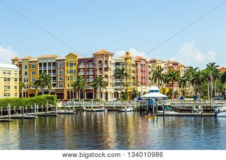 NAPLES, USA - AUG 3, 2013: Colorful Spanish influenced buildings overlooking the water in tropical Naples Florida .