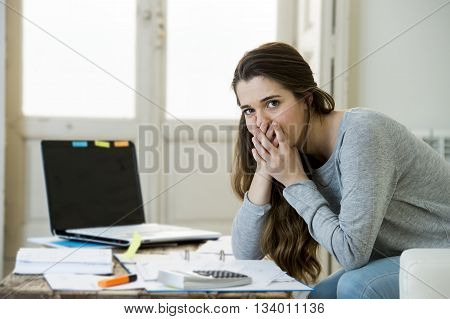 young attractive and desperate woman suffering stress doing domestic accounting paperwork bills and invoices worried and stressed at home sofa couch with laptop computer and bank folders