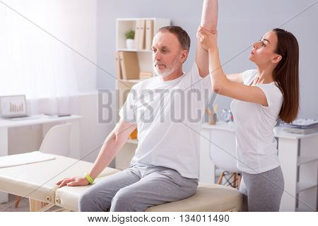 Therapy. Cheerful and busy young female physiotherapist stretching her male patient hand in a medical office