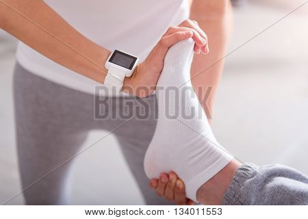 Stretch exercise. Close up of hands of physiotherapist stretching patient sole in a medical office