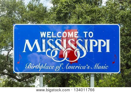 Red white and blue sign to welcome travelers to Mississippi - Birthplace of America's Music