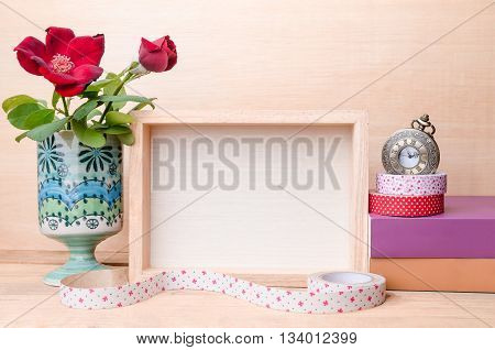 Photo frame with book and flowers on the wooden table