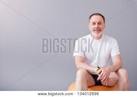 Sporty man. Smiling and cheerful man sitting on a gym ball during physiotherapy and being on a isolated grey background