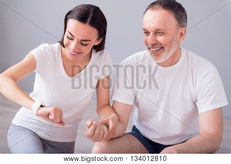 Medical. Smiling and positive physiotherapist taking the pulse  of cheerful male patient during physiotherapy