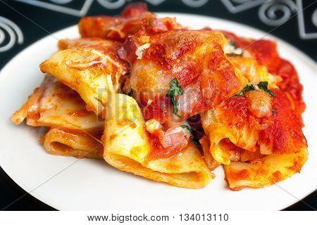 Paccheri baked with tomato sauce mozzarella bacon and basil. Italian culinary specialties.