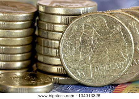 Australian one and two dollar gold coins against a background of notes.
