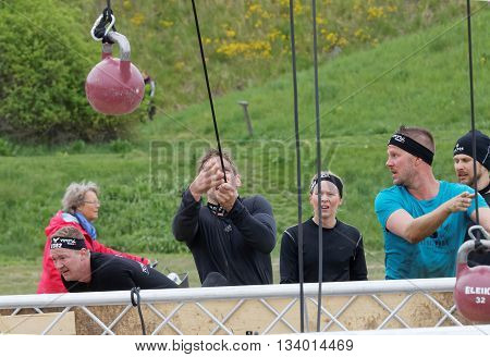 STOCKHOLM SWEDEN - MAY 14 2016: Men fighting to hoist a heavy kettlebell using a rope in the Thor Strength obstacle in the obstacle race Tough Viking Event in Sweden May 14 2016