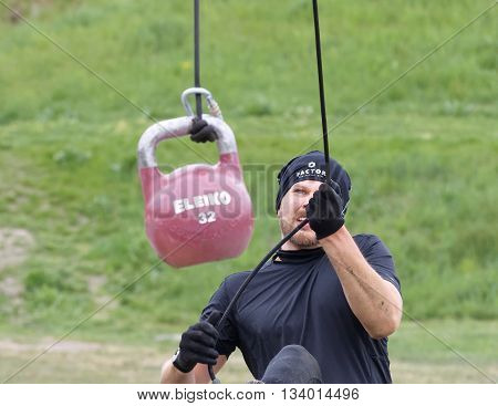 STOCKHOLM SWEDEN - MAY 14 2016: Man fighting to hoist a heavy kettlebell using a rope in the Thor Strength obstacle in the obstacle race Tough Viking Event in Sweden May 14 2016