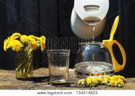 Making tea with dandelions outdoors at noon. Sunlight is bright and shadows are deep. Focus on a glass.