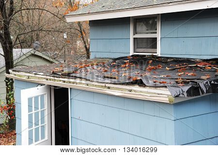 house roof damaged in hurricane storm covered with plastic shield