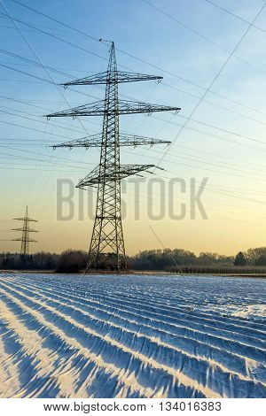 Electrical Tower In Rural Landscape With Fields In Foil
