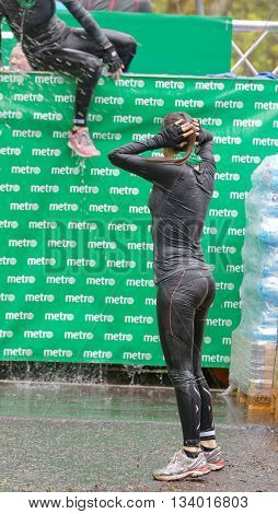 STOCKHOLM SWEDEN - MAY 14 2016: Woman jumping out of a tank of ice cold water in the Ice cube obstacle in the obstacle race Tough Viking Event in Sweden May 14 2016