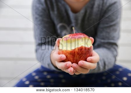 kid hands holding a red bitten apple an apple a day keep the doctor away health concept