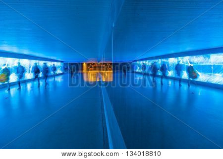 WIESBADEN, GERMANY - APR 3, 2011: tunnel with pedestrians in motion in blue cool light. The tunnel enables pedestrians to cross the main street in Wiesbaden under earth.