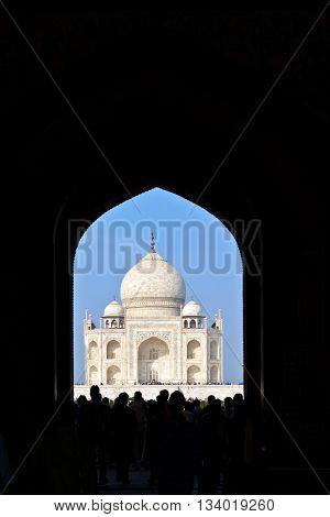 AGRA, INDIA - JUNE 3, 2012: Taj Mahal in India seen througt the entrance gate