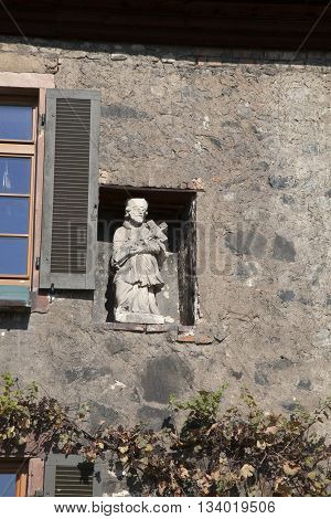 apostle with cross at the wall in the garden