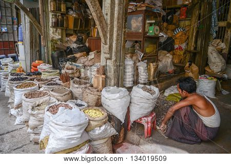 Yangon Myanmar - April 25 2016 : A Burmese men sitting in front on one of spices shop in Thein Gyi Zay market