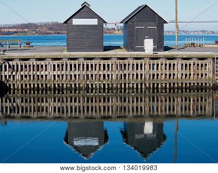 Blue water ripples background - Two small wooden sheds reflected in the water