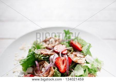 Strawberry and chicken steaks mix with onion copyspace. Top view on plate with mix of grilled chicken steaks, strawberries, onion and mozzarella cheese on white wooden background.