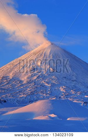 Beautiful winter volcanic landscape of Kamchatka Peninsula: view of erupting active Klyuchevskaya Sopka at sunrise. Eurasia Russian Far East Kamchatka Region Klyuchevskaya Group of Volcanoes.