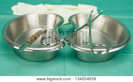 Surgical Clamp And Knife Placed On Kidney Shape Bowl