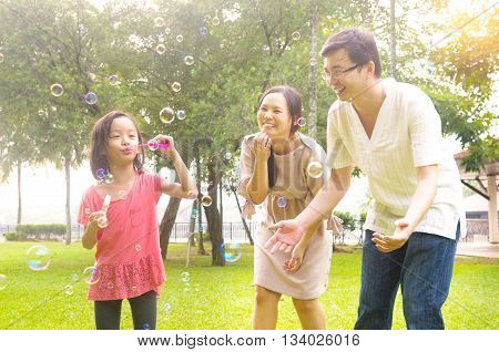Portrait of joyful happy Asian family playing bubbles together at outdoor park during summer sunset.