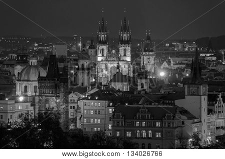Aerial view of illuminated historical buildings of Prague, Czech Republic at Night. Charles bridge and Tyn Church. Black and white