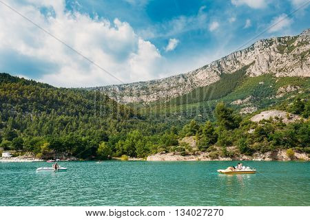 People Floating On Catamarans On The St Croix Lake In The Gorges Du Verdon In South-eastern France. Provence-Alpes-Cote D'Azur. Sunny Summer Day With Blue Sky.