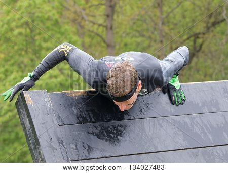 STOCKHOLM SWEDEN - MAY 14 2016: Men climbing over a plank obstracle in the obstacle race Tough Viking Event in Sweden May 14 2016