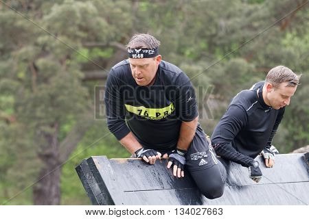 STOCKHOLM SWEDEN - MAY 14 2016: Older men climbing over a plank obstracle in the obstacle race Tough Viking Event in Sweden May 14 2016
