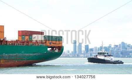 Oakland CA - June 09 2016: Tugboat AHBRA FRANCO at the stern of cargo ship SEASPAN HAMBURG assisting the vessel to maneuver into the Port of Oakland. City of San Francisco in the background.