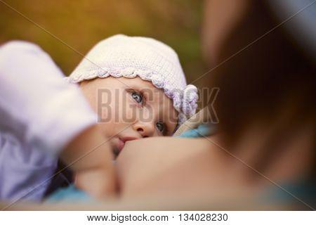 Little baby girl breast feeding outdoor