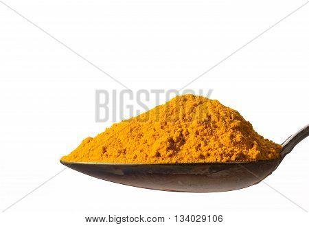Heap of kurkuma powder on spoon isolated on white background closeup.