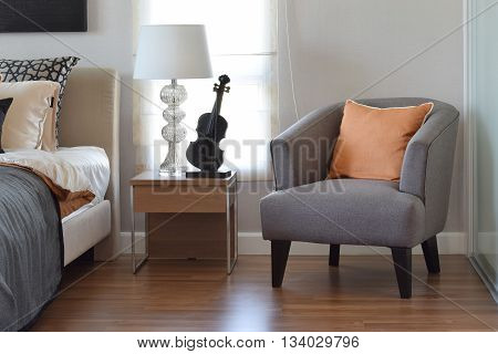 Modern Bedroom Interior With Orange Pillow On Grey Chair And Bedside Table Lamp At Home