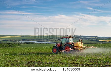 Farm machinery spraying insecticide to the green field agricultural natural seasonal spring background