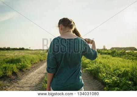 teen girl walking away on dirt rural road between fields, summer time