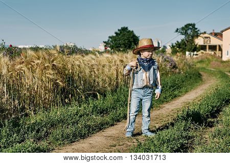 Little boy dressed in Western style in the field , retro style