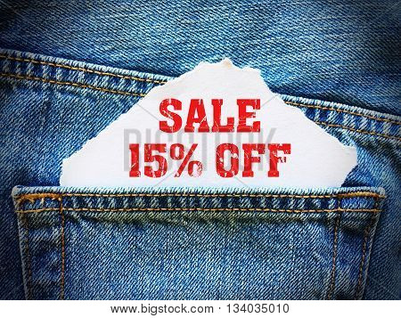 15% off on white paper in the pocket of blue denim jeans