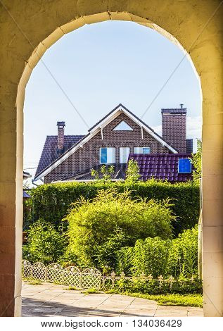 A view of the backyard of a private house through the archway