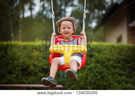 Little smiling boy having fun and swinging on outdoor playground. Happy active childhood.
