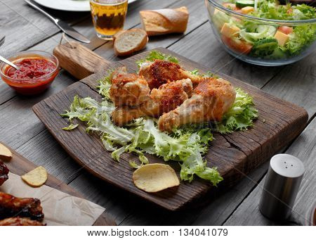 Grilled chicken legs on lettuce leaves on a wooden massive board with sauce