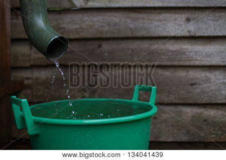 Rainwater shooting from a gutter into a water collecting reservoir
