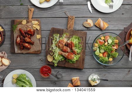 Outdoors Food Concept. On the wooden table different food grilled chicken legs buffalo wings bread salad potatoes top view