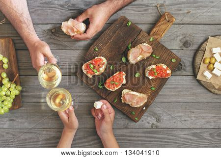 Couple clinking glasses with white wine top view