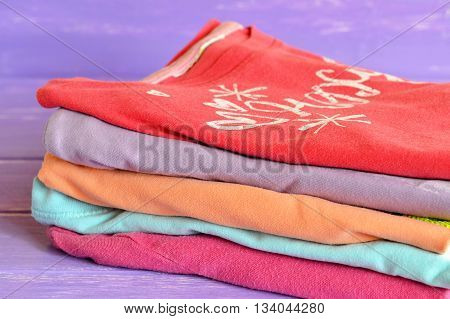 Set of colorful children clothing on lilac wooden background. A stack of stylish bright cotton blouses for girls. Macro.