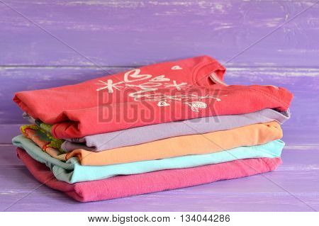 Pile of baby textile clothes. Pink, red, orange, blue, purple clean fabric jackets for girls on wooden background. Close-up