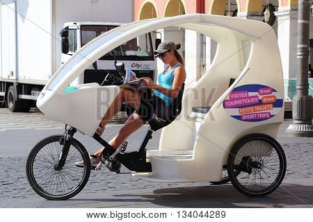NICE, FRANCE - MAY 19, 2015: A strange young girl trishaw is resting while waiting for customers.