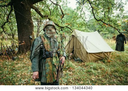 Hidden unidentified re-enactor dressed as World War II german wehrmacht sniper soldier in forest.